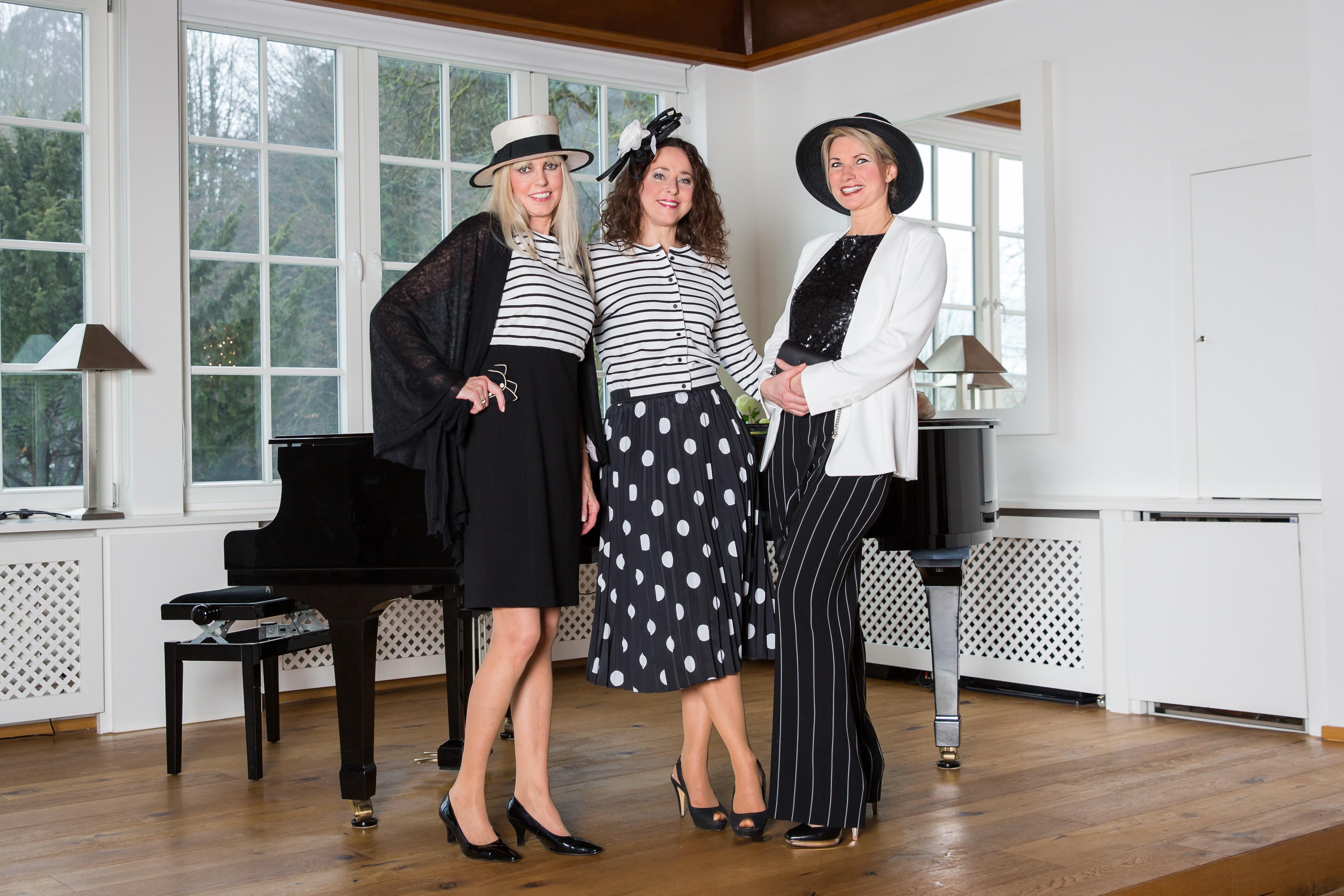 3 Frauen  schwarz/weiß gekleidet mit elegantem Strohhut und Fascinator